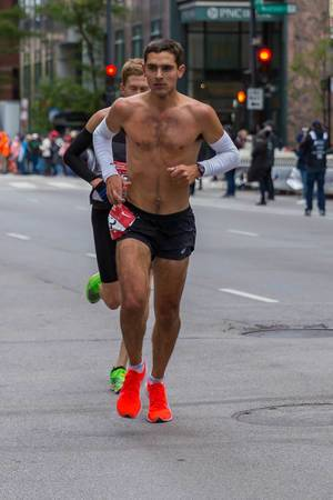 Shirtless runner in black shorts and red running shoes at the 2019 Chicago Marathon
