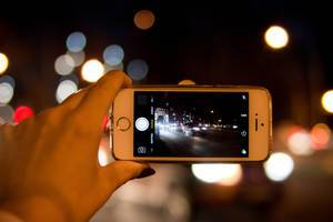 Shooting night Bucharest city by smartphone in hand