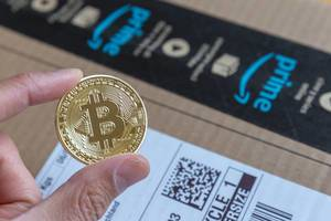 Shopping with Bitcoin on Amazon is no more a fiction - Hand shows gold-colored coin with big Bitcoin logo in the middle