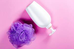 Shower gel and purple washcloth on pink background