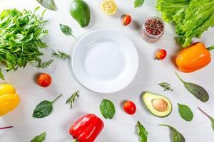 Sicht auf Gemüse, Kräuter und Gewürze um einen weißen Teller herum, als Konzeptbild für eine gesunde Ernährung