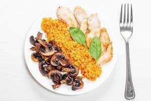 Sicht auf Mittagessen-Teller mit Linsen, Huhn und Pilzen auf weißem Holztisch