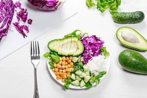 Sicht von oben auf bunten veganen Teller  mit Kichererbsen, weißer Reis und gehacktem frischem Gemüse