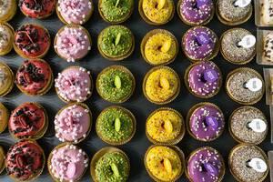 Sicht von oben auf Dots original Rainbow-Donuts mit Pistazien, Yellow Frutti, Marshmallow und Red Cookie