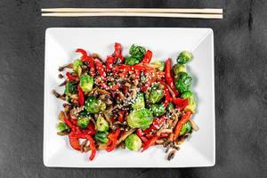 Sicht von oben auf ein Eintopfgericht mit Gemüse, Pilzen, Sesamkörner und Rosenkohl, auf einem Teller neben Essstäbchen
