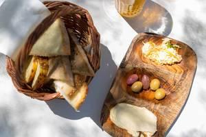 Sicht von oben, auf ein Korb mit verschiedenen Brotscheiben, mehrfarbigen Oliven und Hummus, auf einem Holzbrettchen