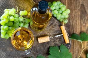Sicht von oben auf ein Weinglas, Weinflasche, Korkenzieher und Weintrauben, auf einer rustikalen Holzoberfläche