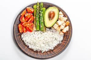 Sicht von oben auf einen Bambusteller mit Reis, Tomaten, Spargel, Avocado und Apfelstücken