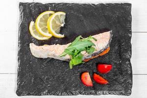 Sicht von oben auf einen gebackenen Lachs mit frischem Rucola, Zitrone und Tomaten, auf einem dunklem Steinbrettchen
