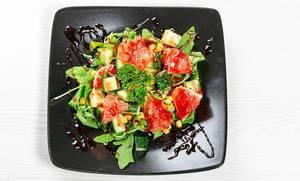 Sicht von oben auf einen gesunden Salat mit Rucola, buntem Gemüse und roten Grapefruitscheiben, auf einem schwarzen Teller