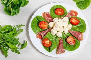 Sicht von oben auf einen grünen Salat mit Schinkenscheiben, Mozzarella, Tomaten und Kräutern auf einer weißen Platte