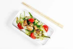 Sicht von oben auf einen Salat mit Gemüse und Pilzen auf einem weißen Teller, neben Essstäbchen