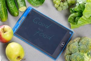 """Sicht von oben auf frisches, reifes Obst und Gemüse, neben der Aufschrift - Gute Lebensmittel - auf grauem Hintergrund"""""""