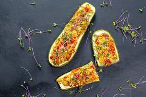 Sicht von oben auf gebakcene Zucchini mit Füllung, buntem Gemüse und Microgreens-Keimsprossen