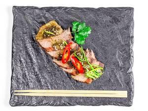 Sicht von oben auf geschnittene Filetstücke aus Rindfleisch, mit Chilischoten, Lauch und Sesamkernen, neben Essstäbchen auf einem schwarzen Schieferstein