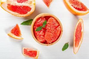 Sicht von oben auf geschnittene Grapefruitscheiben und Fruchtstücke, auf einer weißen Oberfläche