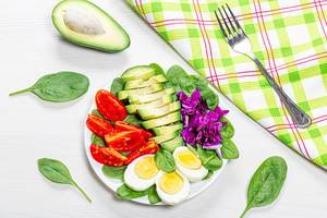 Sicht von oben auf gesunden Frühstücksteller mit gekochten Eiern, frischem Gemüse und Spinatblätter