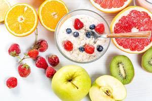 Sicht von oben auf Haferflocken zum Frühstück, mit reifen Beeren, gesundem Obst und halbierten Früchten, auf einem Holztisch