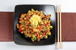 Sicht von oben auf Hähnchenfleisch Gemüse und Pilzen in scharfer Sauce, auf einem schwarzen Teller neben Essstäbchen