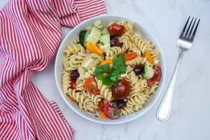 Sicht von oben auf italienischer Nudelsalat mit frischem Gemüse in einer weißen Schüssel