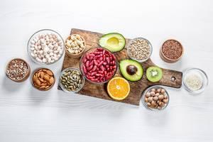 Sicht von oben auf Nussmix, Avocado, Orange und Kiwi auf einem Küchentisch