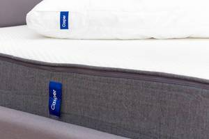 Side view of the breathable and ergnomic Casper mattress in white and grey with Casper pillow