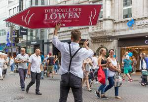 "Sign spinning with ""Die Höhle der Löwen Pop up store"" in a German shopping street"