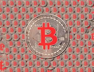 Silberne Bitcoin-Münze vor Hintergrund aus vielen aneinandergereihten Bitcoins