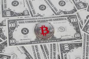 Silberne Münze der Bitcoin Kryptowährung auf 100 USD Banknote