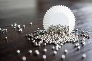 Silberne Streusel auf einem Holztisch