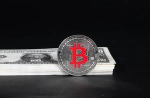 Silberner Bitcoin vor Stapel von US-Dollar Banknoten vor schwarzem Hintergrund