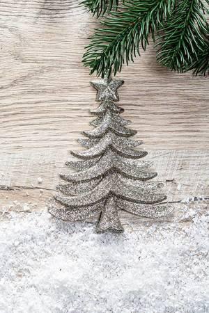 Silberner Weihnachtsbaum mit Kunstschnee vor hölzernem Hintergrund