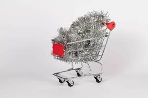 Silberner Weihnachtsbaumschmuck in Einkaufswagen vor weißem Hintergrund