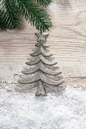 Silver Christmas tree with snow on a wooden background (Flip 2019)