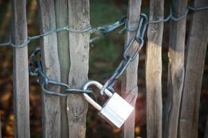 Silver Padlock and Chain closing a Wooden Gate