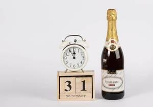 Silvester zum 31. Dezember auf hölzernem Kalender, Wecker auf 5 vor 12 und Champagnerflasche