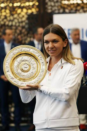 Simona Halep, the 2019 Wimbledon winner, presents the trophy