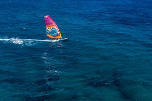Single windsurfer doing watersports in the deep blue Aegean Sea