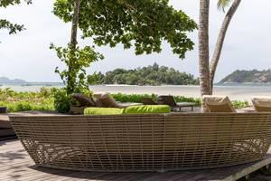 Sitzecke mit Rattanmöbel zum Entspannen unter Palmen mit Blick auf den indischen Ozean und Strand von Mahé auf den Seychellen-Inseln
