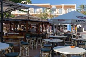 Sitzgelegenheiten und Sonnenschirme an einer Bar auf Mallorca