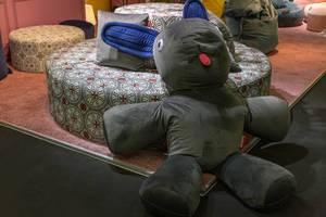 Sitzpuff in Form eines riesigen Hasen lehnt sich an rundes Sofa mit auffälliger Musterung an