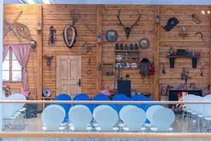 Sitzreihen vor einer im Stil einer bayrischen Berghütte dekorierten Holzwand