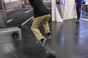 Skater am Huawei Stand führt an der Photokina einen Trick mit dem Skateboard vor