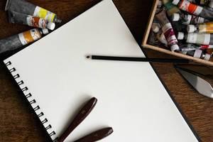 Sketchbook mit Farben, Stiften und Spachteln