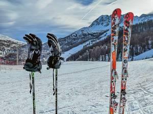 Skiausrüstung wie Paar Ski, Skistöcke und darauf gesteckte Handschuhe auf Skipiste im Winter