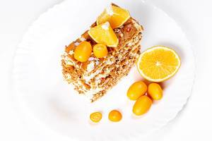 Slice of cake with condensed milk, nuts and citrus, top view (Flip 2020)