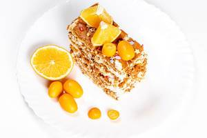 Slice of cake with condensed milk, nuts and citrus, top view