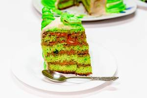 Slice of homemade green cake on a platter with a spoon