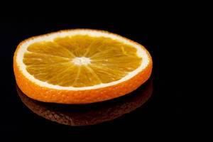 Slice of Orange fruit on the black reflective background (Flip 2019)