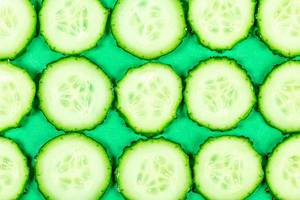 Sliced cucumber slices on a green background, top view